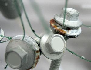 แหวนเหล็กที่เป็นสนิมก่อนตัวสกรู และอาจทำให้เกิดการลุกลามไปยังแผ่นหลังคา